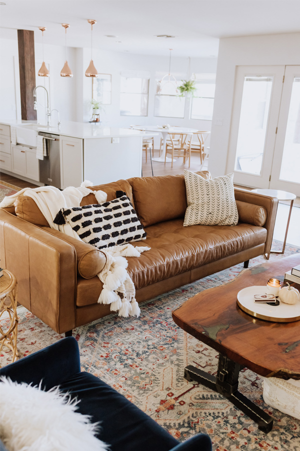 Tan leather modern farmhouse couch in bright airy living room - Design curated by Rare and Worthy Co