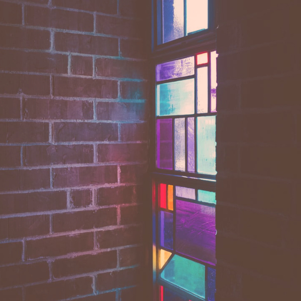 brick wall and stained glass window with light coming through