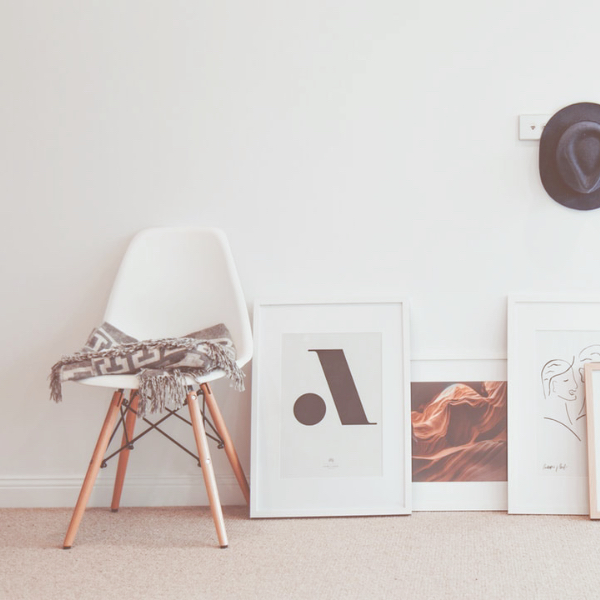 white wall with white modern chair and framed art on floor leaning against wall